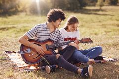 Joyful young couple have fun togehter, sing songs and play guitar, sit on plaid, have happy expressions. Attractive curly male you. Ngster plays music instrument royalty free stock image