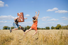 Joyful young couple having fun in wheat field. Excited man and woman running with retro leather suitcase on blue sky Royalty Free Stock Images