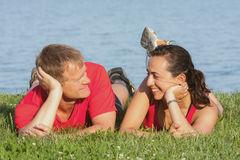 Joyful young couple is overlaping shore of the lake Stock Images