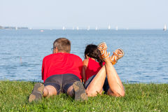 Joyful young couple is overlaping shore of the lake Royalty Free Stock Photography