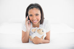 Joyful young dark haired model making phone call while cuddling plush sheep Stock Photos