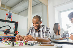 Joyful young designer testing 3d printing. Happy male engineer is working with details of 3d printer in office. He is sitting at desk and making notes. Man is stock photography