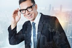 Joyful young entrepreneur smiling. Plans and ambitions. Joyful positive young entrepreneur fixing his glasses and smiling while having lots of plans and Stock Photos