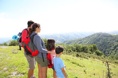 Joyful young family in the mourntains enjoying Stock Photos