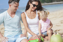 Joyful young family with their little daughter sitting on the be. Close up portrait of joyful young family with their little daughter sitting on the beach and Stock Photos