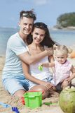 Joyful young family with their little daughter sitting on the be. Portrait of joyful young family with their little daughter sitting on the beach while looking Stock Images