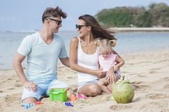 Joyful young family with their little daughter sitting on the be. Portrait of joyful young family with their little daughter sitting on the beach and playing Stock Photography