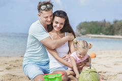 Joyful young family with their little daughter sitting on the be. Portrait of joyful young family with their little daughter sitting on the beach on summer Royalty Free Stock Photo