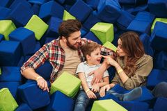 Joyful young family with their little son. Spending time together at the entertainment centre Stock Photos