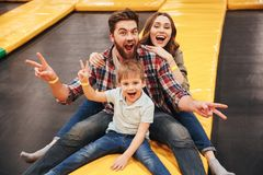 Joyful young family with their little son. Spending time on a trampoline together at the entertainment centre Royalty Free Stock Photography