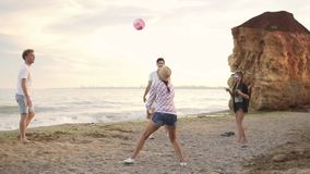 Joyful young friends playing volley ball on the beach by the sea in the evening. Active vacation. Slowmotion shot.  stock video