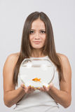 Joyful young girl with an aquarium with goldfish in hands Stock Image