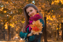 Joyful young girl in autumn Park holds a bouquet of leaves in his hand and smiles Stock Image