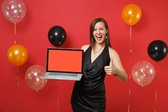 Joyful young girl in black dress showing thumb up and holding laptop pc computer with blank black empty screen on red. Background air balloons. Happy New Year royalty free stock images