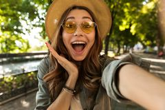 Joyful young girl in hat and sunglasses walking at the park royalty free stock photography