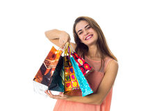 Joyful young girl keeps before a lot of different packages with gifts is isolated on  white background Stock Photography