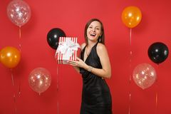 Joyful young girl in little black dress celebrating holding red box with gift, present on red background air balloons stock photography