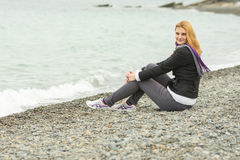 Joyful young girl sitting on pebble beach by the sea on a cloudy cold day Stock Image