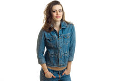 Joyful young girl stands in jeans jacket is smiling looks straight and keeps hands in his pockets royalty free stock images