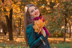 Joyful young girl stands smiling in the Park and keeps the leaves Royalty Free Stock Photo