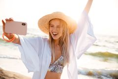 Joyful young girl in summer hat and swimwear. Spending time at the beach, taking a selfie with outsretched hand Royalty Free Stock Photos