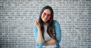 Joyful girl in sunglasses holding lollipop smiling on brick wall background. Joyful young girl in sunglasses is holding lollipop smiling standing alone on brick stock footage