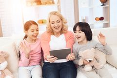 Joyful young grandmother with grandchildren in mood sends greetings to someone on tablet. stock photo