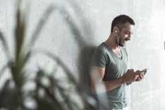 Joyful young guy is listening to music using his phone Royalty Free Stock Image