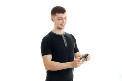 Joyful young guy standing in a black t-shirt and includes music on phone stock photos