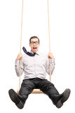 Joyful young guy swinging fast on a swing Royalty Free Stock Photo