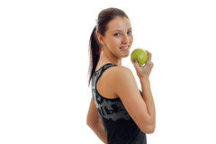 Joyful young gymnast stands sideways and holding a Green Apple close-up stock image