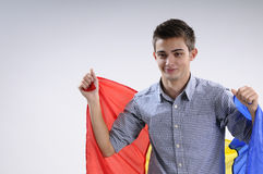 Joyful young man. Happy young man showing romanian national flag Stock Photography