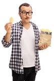 Joyful young man eating potato chips Stock Photo