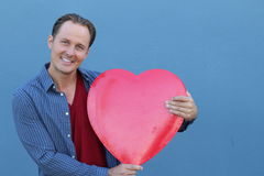 Joyful young man holding a big red heart isolated on blue background Royalty Free Stock Photos