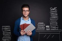 Joyful young man holding diaries. Stock Photos