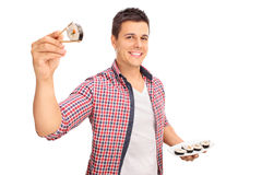 Joyful young man holding a piece of sushi Stock Photography