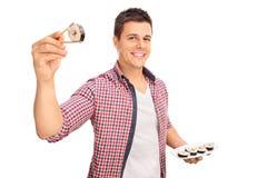Joyful young man holding a piece of sushi Stock Photography