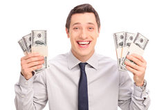 Joyful young man holding six stacks of money Stock Photos