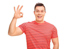 Joyful young man making an OK hand sign. And looking at the camera isolated on white background Stock Images