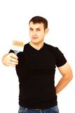 Joyful young man with a paint brush in right hand Royalty Free Stock Photo