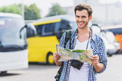 Joyful young man planning his journey. I am ready to travel. Happy male tourist is holding map and smiling. He is standing on bus station Stock Photo