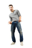 Joyful young man posing with thumbs in pockets Stock Photo