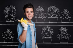Joyful young man relaxing after planting flowers. Royalty Free Stock Image