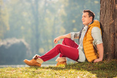 Joyful young man sitting on the grass in a park Stock Photography