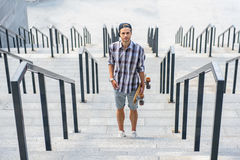 Joyful young man with skateboard on steps. Cheerful male skateboarder is standing on steps and relaxing. He is holding skate and looking at camera with joy Royalty Free Stock Photography