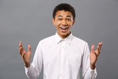 Joyful young man smiling to you. Sincere emotions. Joyful young man standing against black background while smiling to you Stock Photo