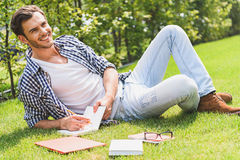 Joyful young man studying in nature Royalty Free Stock Images