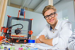 Joyful young man waiting for 3d printing Royalty Free Stock Photography