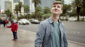 Joyful young man is walking on a sidewalk and listening to music. Young attractive man is walking on a sidewalk in Vegas and listening to music with a smile on stock video footage