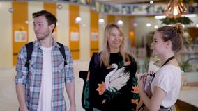 Joyful young man and woman are approaching to cute hostess of a cafeteria in a food court of big mall. She is inviting them and accompanying stock video